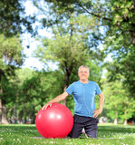 Mogen man med en övningsboll i en parkera Royaltyfri Foto