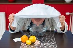 Mogen man med förkylningar och influensa Inandning av örter royaltyfri bild