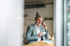 Mogen man med kaffe och smartphonen på tabellen i ett kafé royaltyfri fotografi
