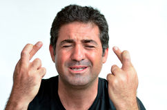 Mogen man med korsade fingrar som hoppas för lycka Royaltyfri Foto
