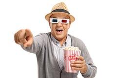 Mogen man med popcorn och exponeringsglas som 3D pekar och skrattar Royaltyfri Foto