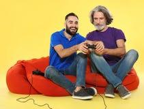 Mogen man och grabb som spelar videospel med kontrollanter royaltyfri bild