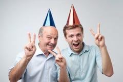 Mogen man och hans ung son som firar den lyckliga födelsedagen som bär roliga lock arkivbilder