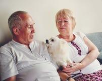 Mogen man och kvinna 60-65 år gammalt sammanträde på soffan och holen Arkivfoto