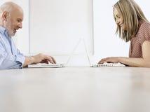 Mogen man och kvinna som använder bärbara datorer royaltyfria bilder