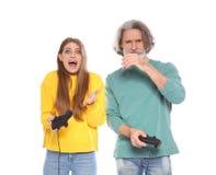Mogen man och ung kvinna som spelar videospel med isolerade kontrollanter royaltyfri bild
