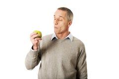 Mogen man som äter ett äpple Royaltyfri Foto