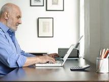 Mogen man som använder bärbara datorn på studietabellen Royaltyfri Fotografi