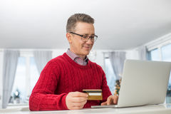 Mogen man som använder kreditkorten och bärbara datorn för att shoppa direktanslutet under jul Royaltyfri Bild