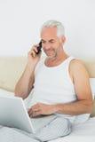 Mogen man som använder mobiltelefonen och bärbara datorn i säng Arkivfoton