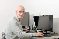 Mogen man som arbetar med hans dator arkivbild