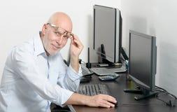 Mogen man som arbetar med hans dator fotografering för bildbyråer