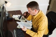 Mogen man som arbetar på hans inkomstskatter medan i kontoret Arkivfoton