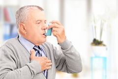 Mogen man som behandlar astma med inhalatorn Arkivbild