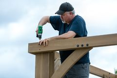 Mogen man som bygger träkonstruktion arkivbilder