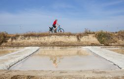 Mogen man som cyklar bredvid den Isla Cristina saltworksen, Spanien Arkivbilder
