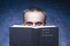 Mogen man som fokuseras och hakas av boken Jultomten I kan förklara Royaltyfri Bild