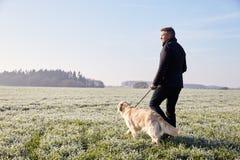 Mogen man som går hunden i Frosty Landscape Arkivbilder