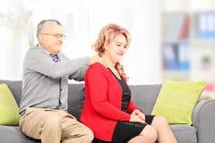 Mogen man som ger massage till hans fru som placeras på soffan Arkivbilder