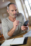 Mogen man som hemma använder smartphonen och bärbara datorn Royaltyfri Fotografi