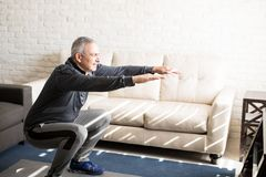 Mogen man som hemma gör squatsgenomkörare arkivbild