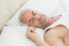 Mogen man som hemma sover i säng Arkivbild