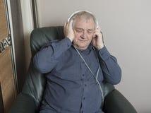 Mogen man som kopplar av och att lyssna till musik Royaltyfria Bilder