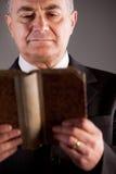 Mogen man som läser en forntida bok Fotografering för Bildbyråer