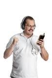 Mogen man som lyssnar till musik på hörlurar Arkivbilder