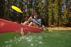 Mogen man som paddlar en kajak i en sjö Royaltyfri Foto