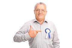 Mogen man som pekar till ett emblem på hans skjorta fotografering för bildbyråer