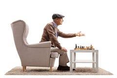Mogen man som placeras i en fåtölj som spelar en lek av schack och arg arkivfoton