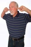 Mogen man som pluggar hans öron Arkivbild