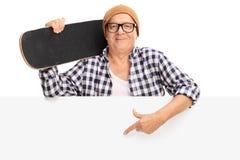 Mogen man som rymmer en skateboard bak en panel Arkivfoton