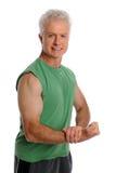 Mogen man som slader bicepsen royaltyfria foton