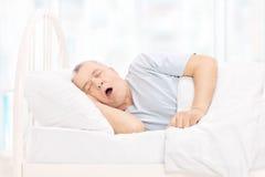 Mogen man som sover i en bekväm säng Royaltyfri Foto