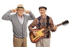 Mogen man som spelar en gitarr med en annan man som pluggar hans öron Arkivfoto