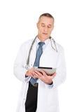 Mogen manlig doktor som använder en minnestavla Royaltyfri Fotografi