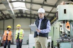 Mogen manlig inspektörhandstil på skrivplattan medan arbetare i bakgrund på bransch Royaltyfria Foton