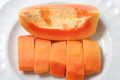 Mogen papaya som skivas i den vita plattan Arkivbild