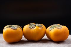 Mogen persimonfrukt på svart bakgrund royaltyfri foto