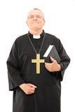 Mogen präst som rymmer en bibel och ser upp Arkivfoton