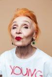 Mogen rödhårig manmodekvinna som blåser kyssar Arkivbild