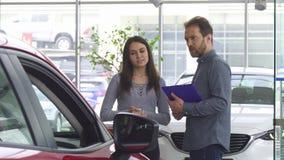 Mogen representant som talar till hans kvinnliga kund som erbjuder henne en bil arkivfoto