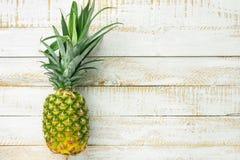 Mogen saftig hel ananas på den vita trätabellen Begrepp f?r semester f?r lopp f?r strikt vegetarian f?r vitaminer f?r livsstil f? arkivfoto