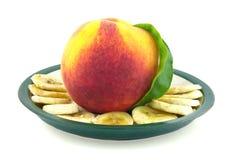 Mogen saftig persika på en platta royaltyfria foton