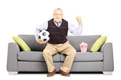 Mogen sportfan som rymmer en fotbollboll och håller ögonen på sporten Royaltyfri Foto