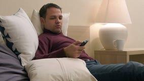 Mogen stilig man som kopplar av i hans hotellrum som söker efter något att hålla ögonen på på TV lager videofilmer
