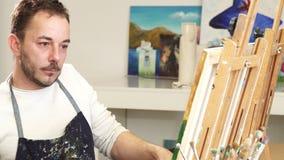 Mogen stilig manlig konstnär som ler samtal på telefonen, medan måla lager videofilmer