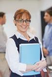 Mogen student för nöjd kvinnlig som poserar i klassrum Royaltyfri Foto
